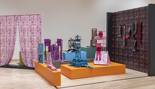 A gallery view of pieces of fiber art—bright, colorful curtains and a series of sculptures with hands in gloves peeking out from their bottoms