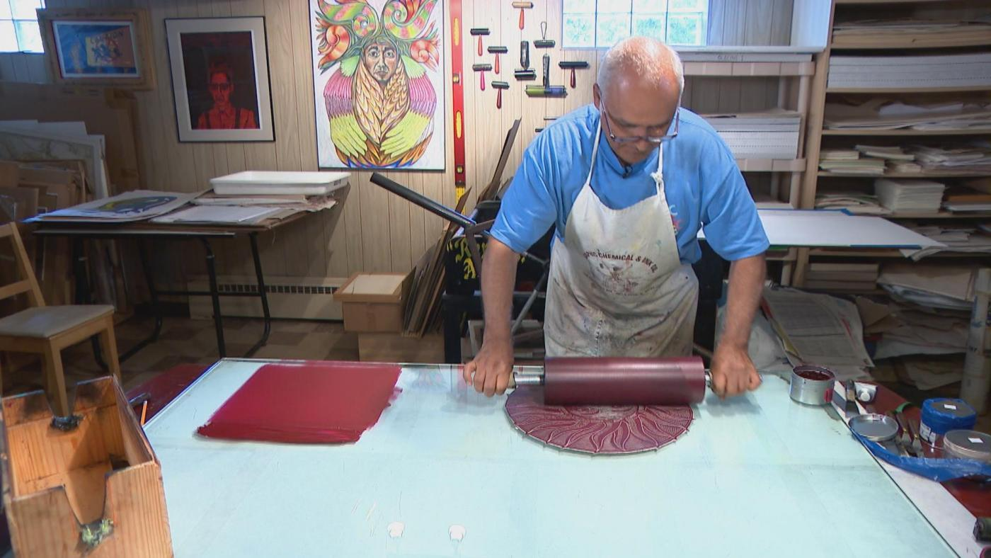 a bald man wearing an apron and blue shirt stands at their workstation, working on a print