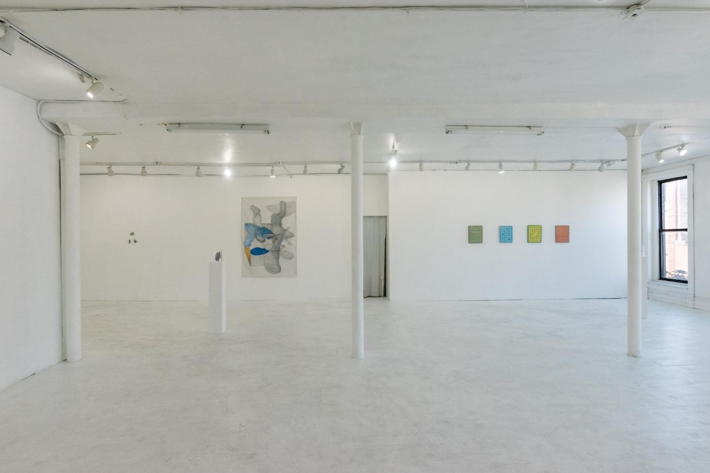 A gallery space with white walls and floors. A few pieces are hung on a wall.