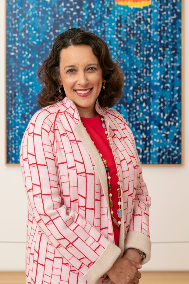 A woman with shoulder-length brown hair, wearing a red-and-white coat, a red top, and round multicolored beads that extend past the length of the photo smiles at the camera in front of a dark blue painting depicting trees on a starry night.