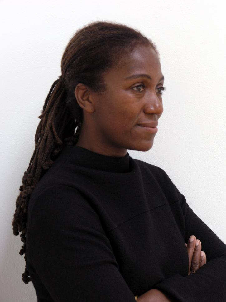 A black woman with long braids wearing a black shirt standing in profile against a white background.