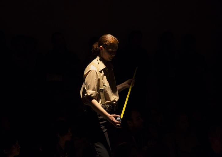 A student performing a piece of performance art on a dark stage