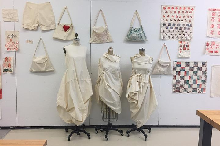 Student work in fashion on display including draped dress forms and hanging bags