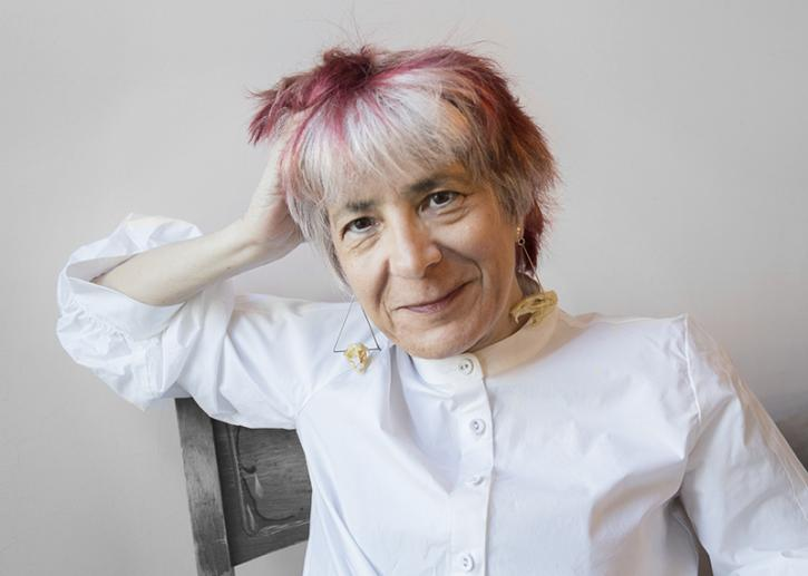 A white woman with short white hair with subtle lowlights, geometric earrings, and a crisp white collarless shirt poses seated, resting one arm on the back of her chair and smiling warmly.