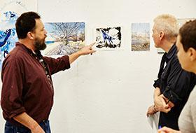 Faculty member discusses artwork with students
