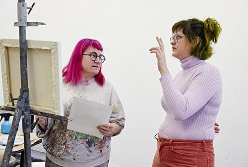 Student and faculty discuss paining