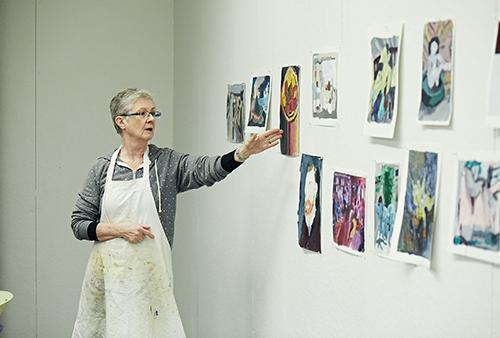 Woman stands in front of wall of oil paintings in apron and discusses one image