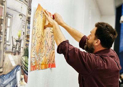 Faculty member mounts artwork to wall