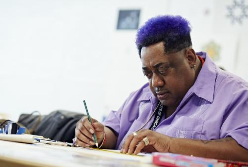 Man in purple shirt sits at table and draws