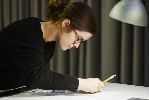 Woman sits at drafting table and works on interior design project