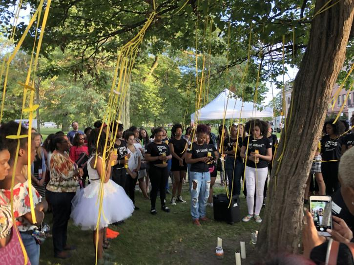 A crowd standing around a tree in a position of mourning. The tree is decorated with yellow streamers