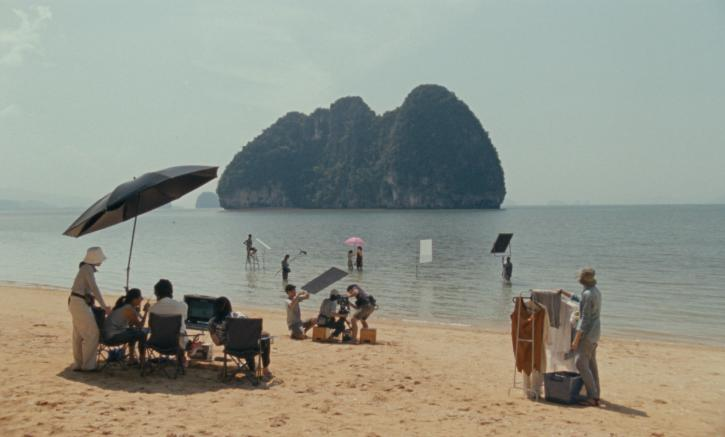 A crew of Thai filmmakers on a film shoot on a beach. Three makers sit under an umbrella in the foreground. Another stands next to a rack of clothing. In the distance two actors stand under a pink umbrella in the ocean water.
