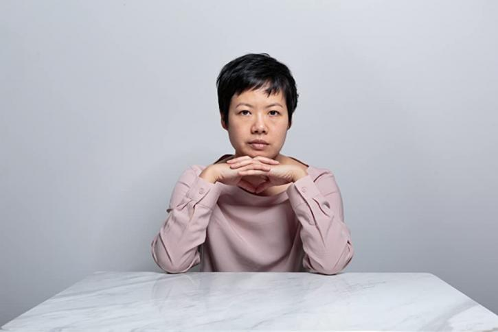 A Thai woman with short black hair sitting at at white table with her hands clasped under her chin looking directly at the camera.