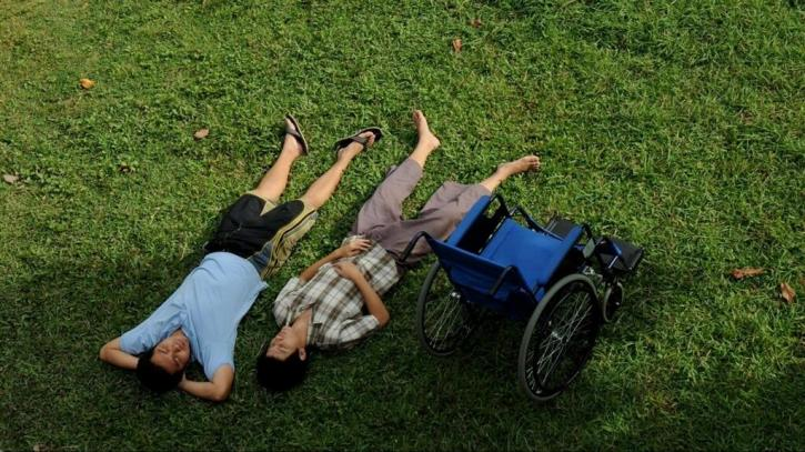 Two men laying in the grass with a blue wheelchair next to them photographed from above.