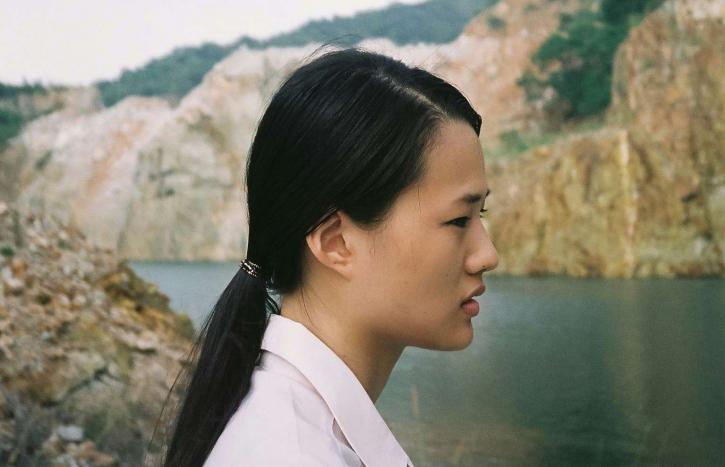 A Thai woman with a low ponytail wearing a white shirt standing in profile against a river landscape.
