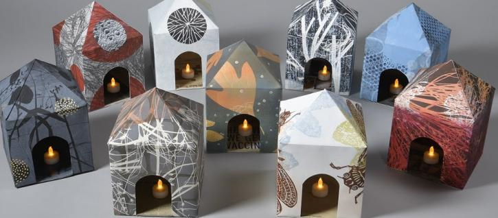 Small houses made out of patterned paper holding candles