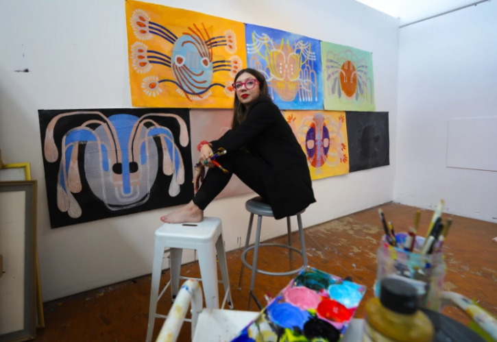 An artist sits in in her studio in front of brightly colored paintings