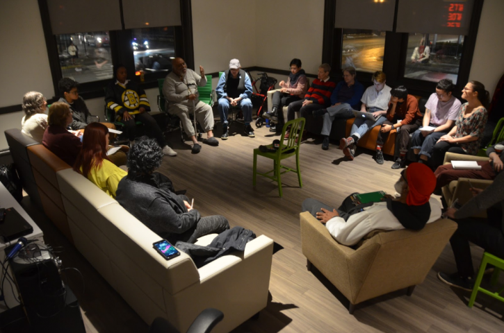A group of students, faculty, and guests sit in a circle having a dialogue at the Center on Halsted