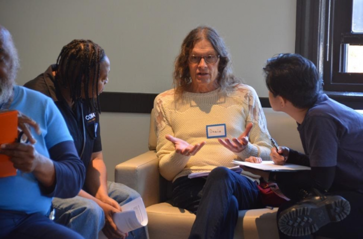 Three seated individuals engage in a conversation at the Center on Halsted