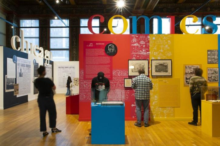Several guests looking at the colorful walls of Ware's exhibition