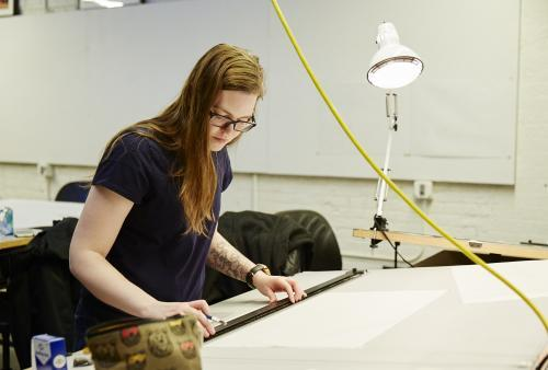Woman stands at drafting table making measurements