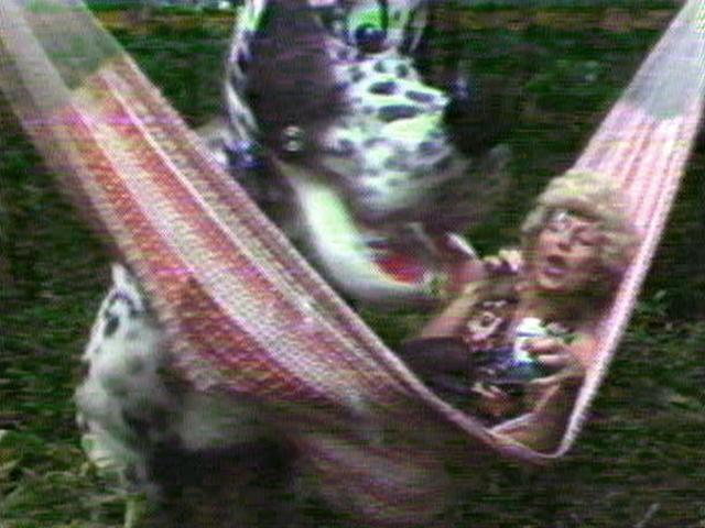 A person in a large dog costume stands over a white woman in a hammock, who is laughing.