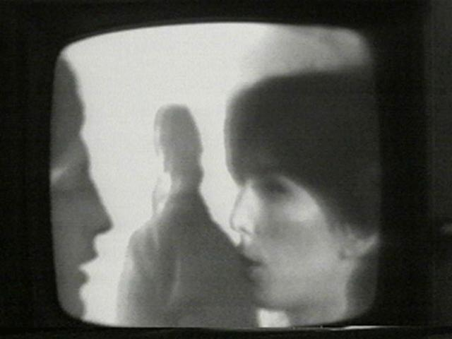 A white man and white woman in profile and another white man in the background with his back turned. All three appear to be photographed off of a television set.