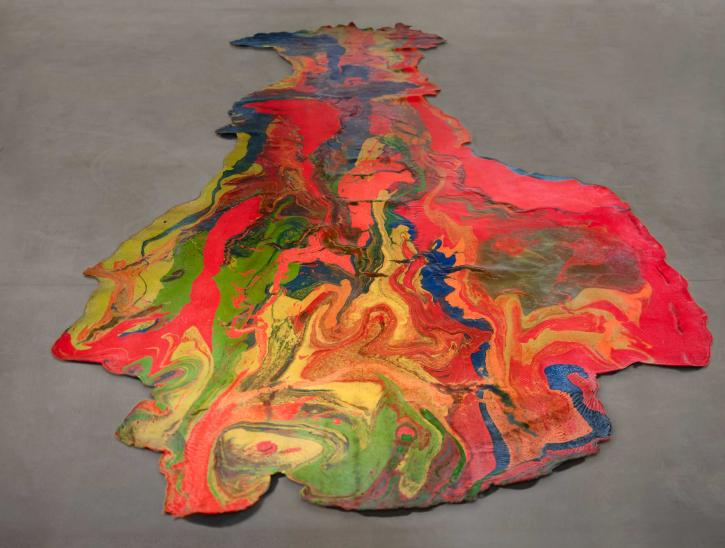 A flat, marbleized latex artwork poured directly on the floor. Colors of red, bright pink, green, blue, and yellow dominate.