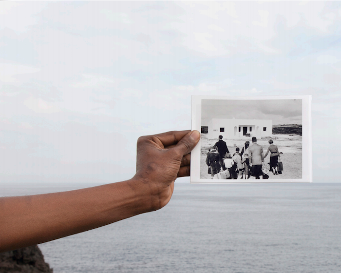 A hand holds up a black and white photo of a family with suitcases arriving at a white house before a vista of open water