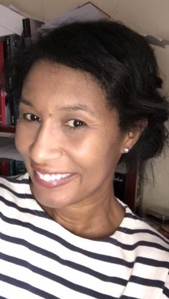 A three-quarter portrait of Romi Crawford, a Black art historian and professor smiling. She wears a striped black and white top, pearl earrings, with her long black hair tied back. In the background are books and a white wall.