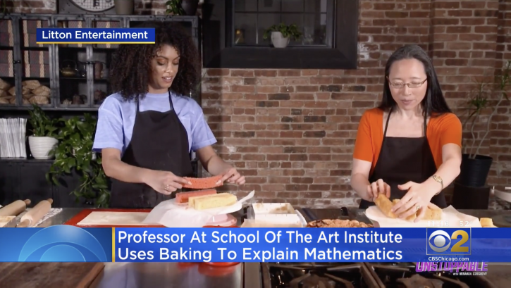 A still from a television program where two women are wearing aprons and baking together