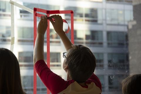 Student drawing with tape on glass.