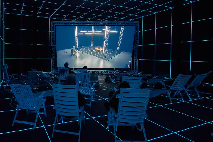 Hito Steyerl, Factory of the Sun, 2015, single channel high definition video, environment, luminescent LE grid, beach chairs, 23 minutes. Installation view, Venice Biennale, German Pavilion, 2015.