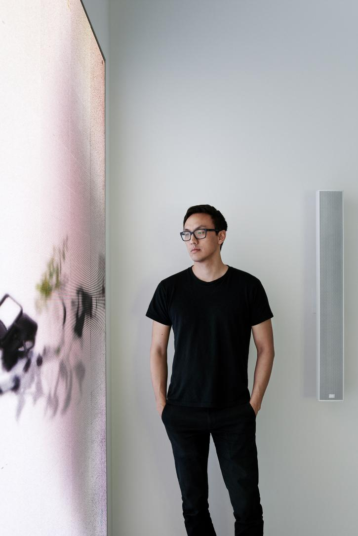 A portrait of the Asian artist Ian Cheng standing, wearing black eyewear, a black tee-shirt, and black pants. His forearms are visible and his hands are inserted in his pant's pockets. To the left of him is a white digital screen that illuminates his face