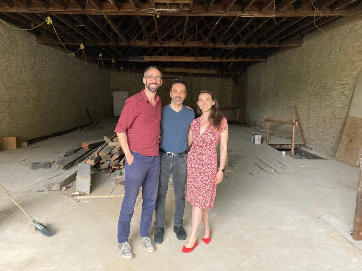 Three individuals stand in a cavernous space under construction