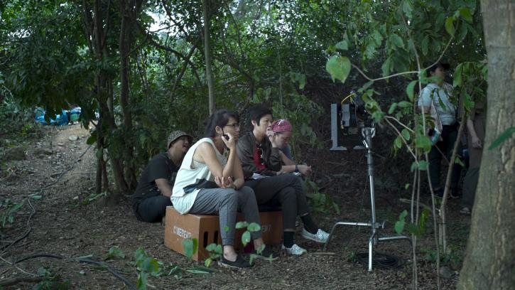 Four people sitting on cardboard boxes in front of a camera monitor in a jungle setting.