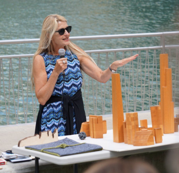 A woman gives a talk in front of a river