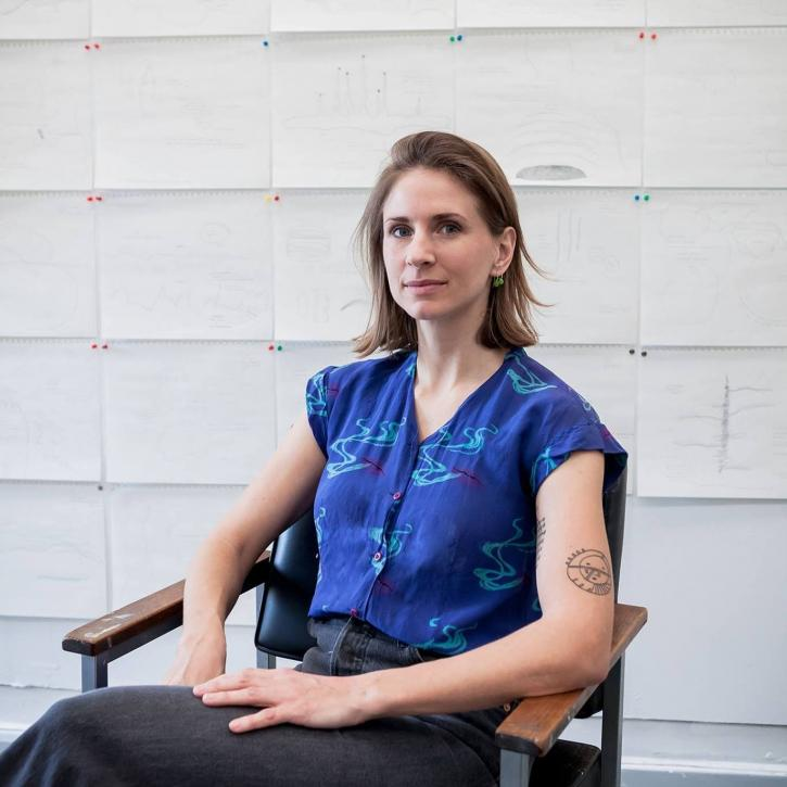 A white woman is sitting with her legs crossed, looking into the  camera. She has dark blonde shoulder length hair and a blue short-sleeved shirt. Behind her are multiple pages of diagrams and drawings tacked to the wall with colorful thumb tacks.