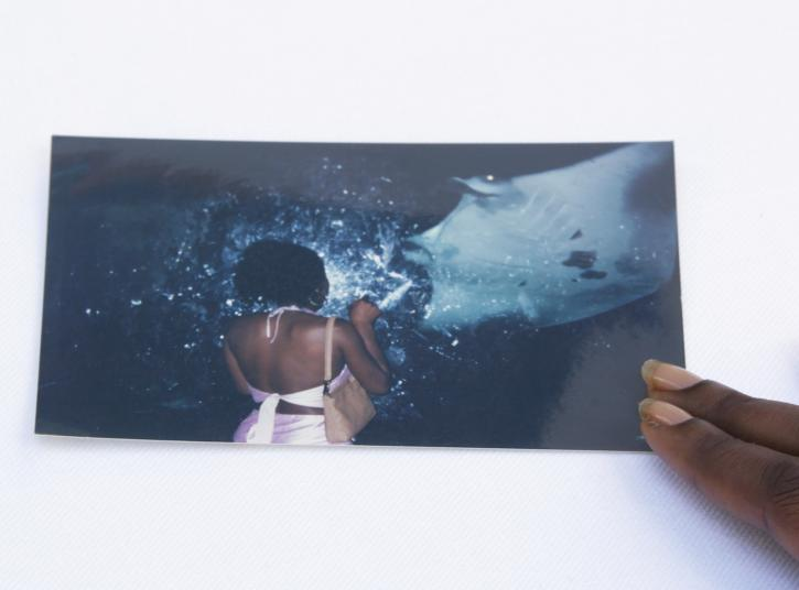 A color printed photograph is pinned down by two fingers of a Black person against a white surface. The photograph shows a Black woman with her back turned. She wears a pink top that exposes her back with a brown handbag slung on her right shoulder.