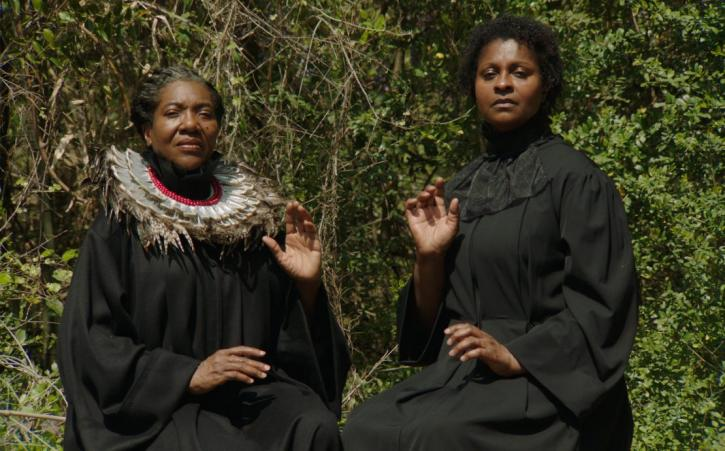 Two Black women dressed in black garments are seated next to each other, performing similar hand gestures and stare directly at the camera.