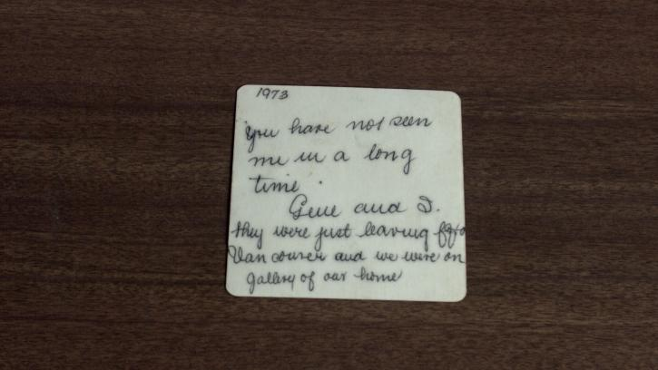 A square white piece of paper rests on a brown wood surface. Written in cursive is a sentence inscribed with black ink.