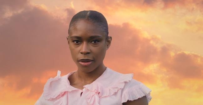 A portrait of a Black woman gazing directly at the camera with black hair slicked back. She wears a light pink top with frills on its collar and shoulder. The background is an orange-colored sky with purple-hued clouds.
