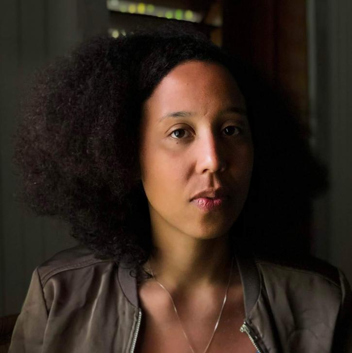 A close-up portrait of the Black filmmaker Madeleine Hunt-Ehrlich gazing directly at the camera. She has voluminous dark brown hair, wears a silver chain drooping down her neck, and a reflective brown bomber jacket. The background is blurred.