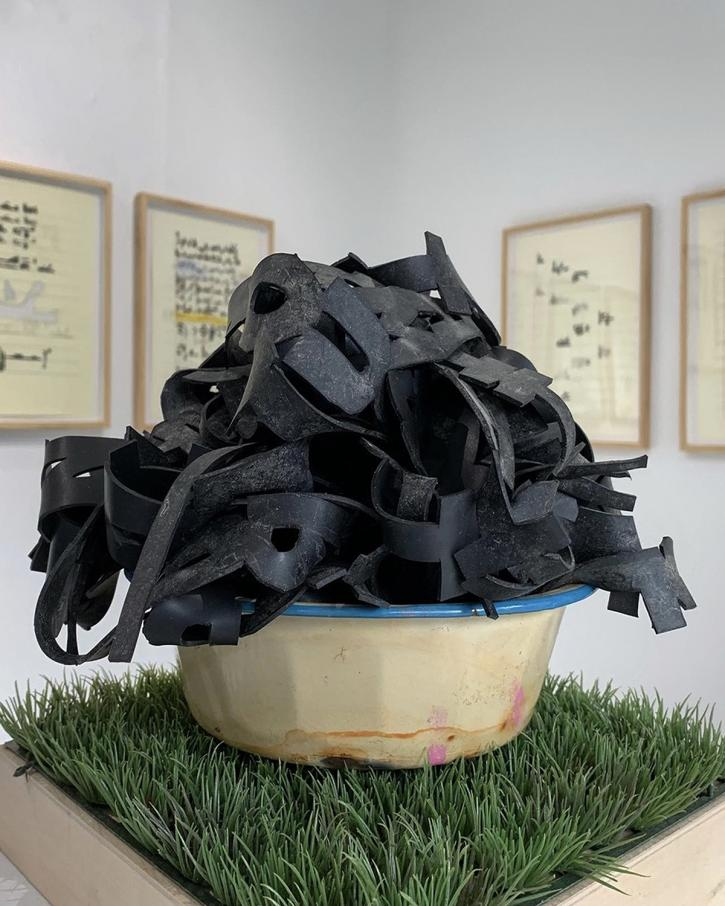 Nyugen E. Smith, Installation view: Masta My Language (Poem in Poem), 2015–19, rubber poem in found bowl on plastic grass and wood, dimensions variable.