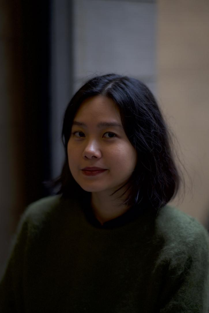 An Asian woman with chin length black hair, and a fuzzy textured green sweater gazes into the camera with a subtle smile. Behind her is a blurry background that appears to be the inside of a building.