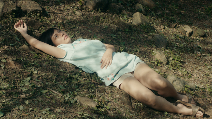 A Thai woman in white shorts and a blue shirt laying languidly on the ground and gazing into the distance.