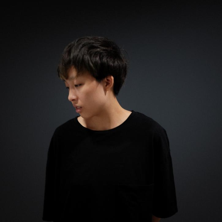 A Thai woman with short black hair in semi profile looking down. The lighting is dramatic.