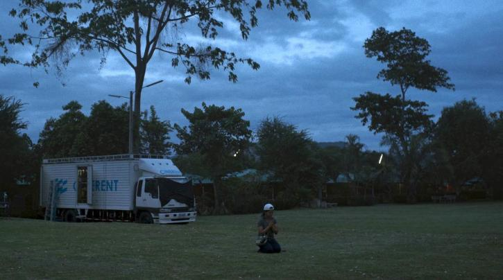 A Thai woman in a white backwards baseball cap kneeling in an outdoor field at dusk. Behind her is a white truck and tall trees.
