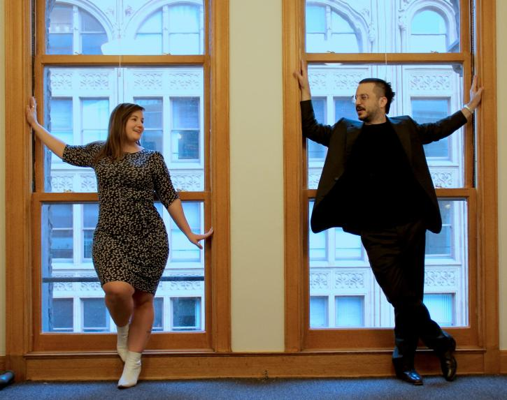 A man and a woman stand in front of a large window in a building in a city