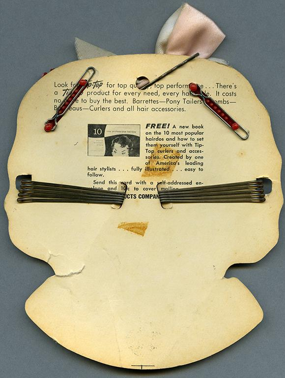 Reverse side of hair clips and holder of a girl's face from the RBSC archive
